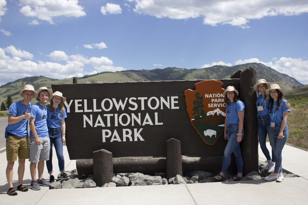 People standing around the Yellowstone National Park sign.
